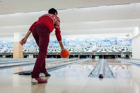 Bowling game. Man having fun playing bowling in club throwing ball on lane. Kegling entertainment. Hobby concept