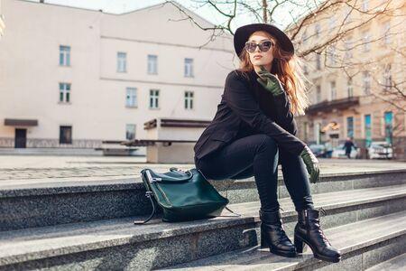 Stilvolle Frau mit Hut, Brille mit grüner Handtasche und Handschuhen, die draußen auf der Straße sitzen. Frühlingskleidung, Accessoires. Weibliche Mode.