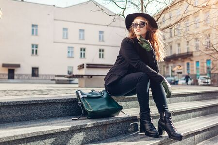 Stylish woman wearing hat, glasses with green handbag and gloves sitting on street outdoors. Spring clothes, accessories. Female fashion.