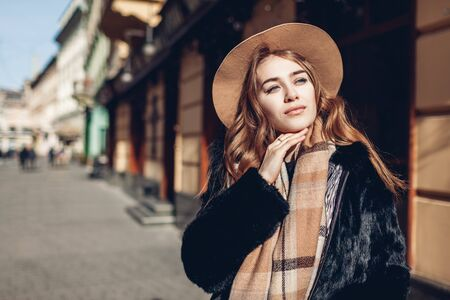 Female fashion. Stylish woman wearing fur coat, beige hat and scarf. Spring accessories. Portrait of young girl on street outdoors