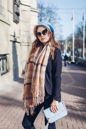 Female fashion. Stylish woman holding purse, wearing beret, sunglasses and scarf outdoors on city street. Spring accessories. 免版税图像