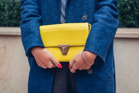 Fashionable purse. Female spring accessories. Stylish woman wearing blue coat and holding yellow handbag outdoors on city street. Close up