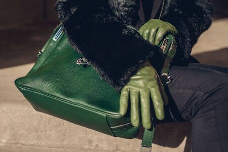 Stylish purse. Fashionable female accessories. Woman with green handbag wearing gloves and fur coat outdoors. Close up