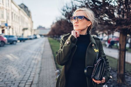 Portrait of stylish young woman in coat sunglasses with purse outdoors on city street. Spring fashion female clothes accessories. Trendy modern outfit
