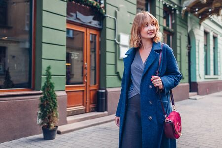 Stylish young woman wearing trendy outfit blue coat walking with purse outdoors. Spring fashion female accessories 免版税图像