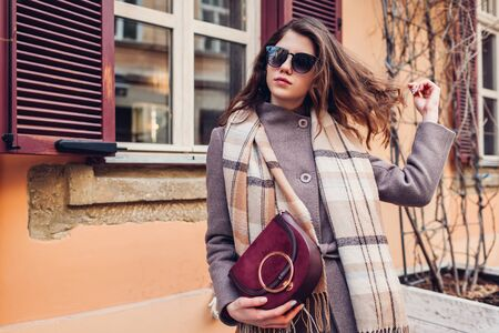 Portrait of stylish happy woman wearing scarf coat sunglasses holding red purse outdoors.