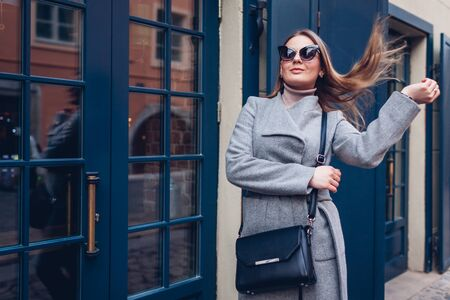 Portrait of stylish woman walking wearing coat sunglasses with purse by cafe showcase outdoors. 版權商用圖片