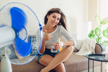 Happy young woman cooling down by ventilator at home drinking water showing thumb up. Summer heat. Archivio Fotografico