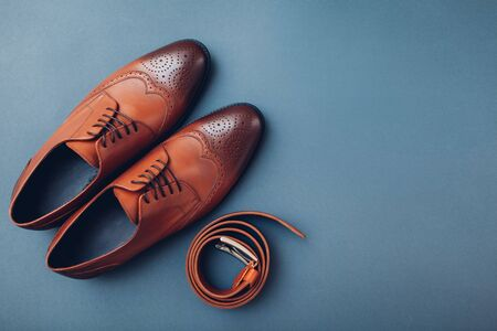 Oxford male brogues shoes with accessories. Men's fashion. Classical brown leather footwear with belt. Top view. Space