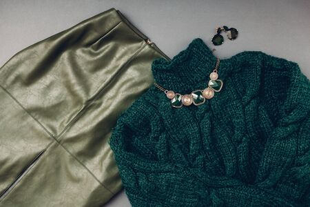 Fashion outfit for woman. Trendy eco leather green skirt, sweater, jewellery on grey background. Spring female clothes accessories. 版權商用圖片