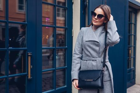 Beauty portrait of stylish woman walking wearing coat sunglasses with purse by cafe showcase outdoors. Spring fashionable female accessories. 免版税图像