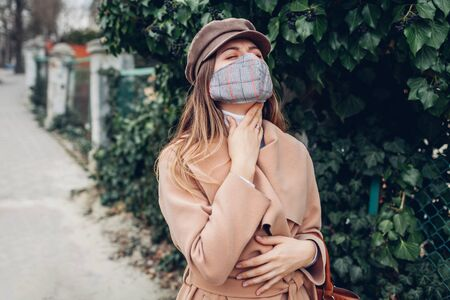 Woman feels sore throat wears reusable mask outdoors during coronavirus covid-19 pandemic. Girl feeling sick spreading flu. Stay safe, keep distance Banque d'images