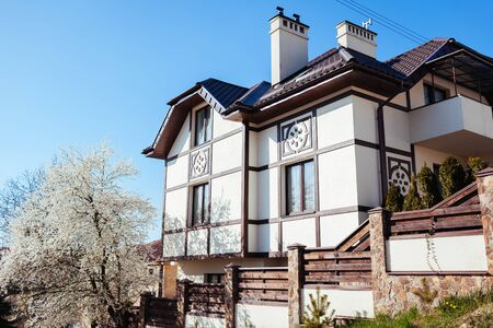 Front view of white rustic scandinavian house with brown roof and plum tree in blossom in spring. Modern europian architecture. Exterior design