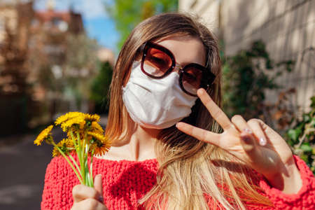 Woman wears reusable handmade protective mask outdoors during coronavirus covid-19 pandemic on empty street. Girl standing alone looking at camera Archivio Fotografico
