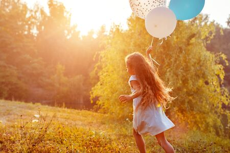 Pretty little girl running with baloons in hand. Kid having fun in summer park. Outdoors activities
