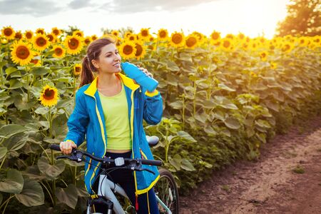 Young happy woman bicyclist drinking water after riding bicycle in blooming sunflower field at sunset. Standard-Bild - 147982995