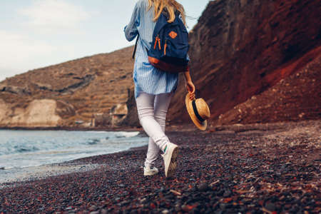 Tourist walking on Red beach on Aegean sea coastline in Akrotiri, Santorini island, Greece. Woman with backpack traveling. Close up of legs