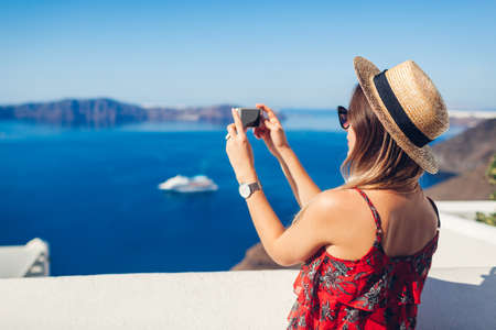 Santorini traveler woman taking photo of sea islands landscape on smartphone. Tourism, traveling, summer vacation