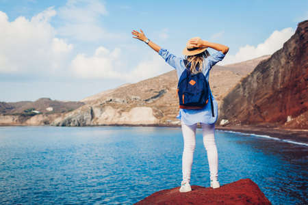 Summer vacation. Happy traveler woman feels free raising arms on rock on Red beach on Santorini island, Greece enjoying landscape. Archivio Fotografico