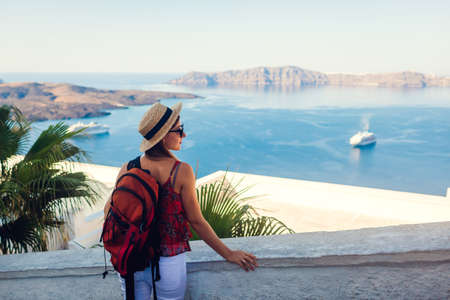 Woman traveler looking at Caldera from Fira, Santorini island, Greece. Tourist with backpack admiring sea landscape with cruise ships.