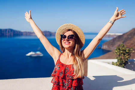 Woman traveler walking raising hands feeling free and happy in Thera, Santorini island, Greece. Girl admires sea landscape. Tourism, traveling, summer vacation