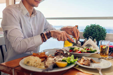 Man eats fish with vegetables in outdoors restaurant served with drinks. Fresh seafood dinner with sea landscape. Summer vacation