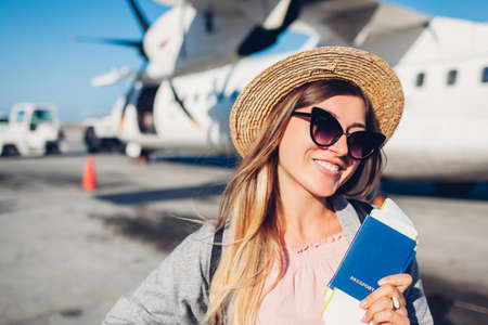 Woman traveler boarding on plane holding passport tickets. Happy passenger with backpack ready for flight. Summer vacation. Renewal of flights Archivio Fotografico