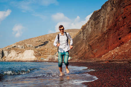 Happy tourist running on Red beach by sea on Santorini island barefooted. Man with backpack traveling enjoying landscape Archivio Fotografico