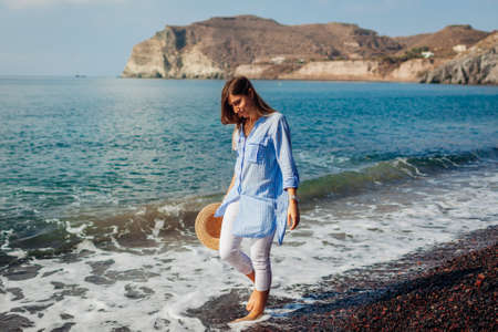 Tourist woman walking on coastline of Red beach Santorini island Greece barefooted. Traveling and summer vacation