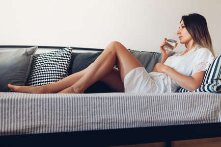 Woman relaxing at cozy home in living room sitting on couch drinking water. Morning routine Archivio Fotografico