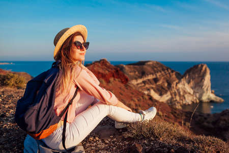 Traveler hiker woman relaxing on mountain top enjoying sea landscape on Santorini island. Summer vacation Archivio Fotografico - 152824617