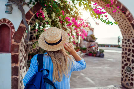 Woman traveler walks along traditional village architecture on Santorini island. Tourist admires flowers. Summer