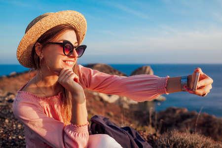 Tourist taking selfie on phone on sea and mountain background on Santorini island, Greece. Hiker on vacation Archivio Fotografico - 152824619