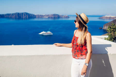 Summer vacation. Woman traveler looks at Caldera from Fira, Santorini island, Greece enjoying sea view. Tourism Archivio Fotografico - 152824620