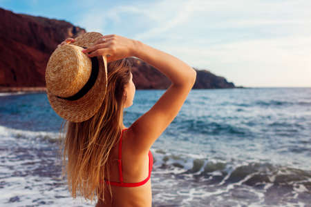 Young woman in bikini and hat relaxing on Red beach in Santorini, Greece. Girl enjoying sea and mountain landscape Archivio Fotografico - 152824621