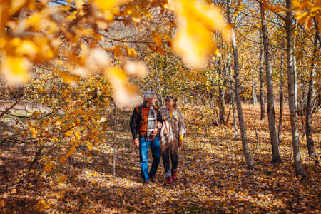 Fall season walk. Senior family couple walking in autumn park. Man and woman relaxing outdoors