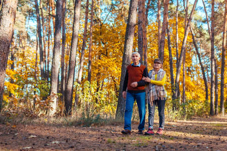 Fall activities. Senior family couple walking in autumn park. Man and woman chilling outdoors enjoying nature
