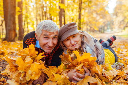 Fall family activities. Senior man and woman lying on heap of leaves in autumn park. People having fun outdoors