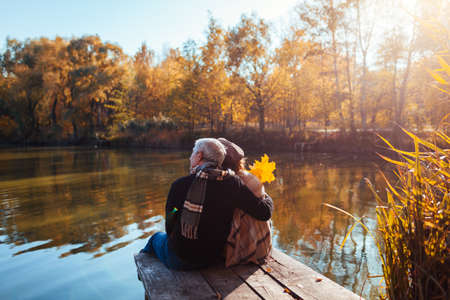 Senior family couple relaxing by autumn lake. Man and woman enjoying natural landscape and hugging sitting on pier Archivio Fotografico