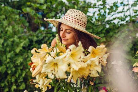 Young woman smelling flowers in summer garden. Gardener taking care of lilies. Girl growing plants. Gardening concept