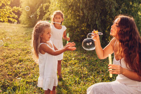 Mother and daughters blow soap bubbles in summer park. Kids having fun playing, catching bubbles having fun outdoors. Family spending time together