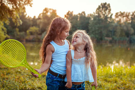 Little girls having fun outdoors after playing badminton. Sisters smiling with rackets in summer park. Kids walking. International Childrens Day