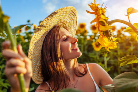 Young happy woman walking in blooming sunflower field wearing hat feeling free smelling flowers and admiring landscape. Summer vacation
