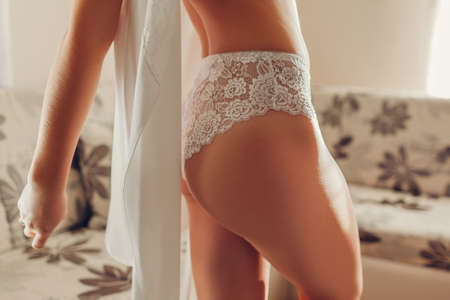 White high-waist panties on sportive booty. Slim woman wearing sexy lace underwear and dressing gown at home. Healthy young female body. Beautiful smooth skin Archivio Fotografico - 152824656