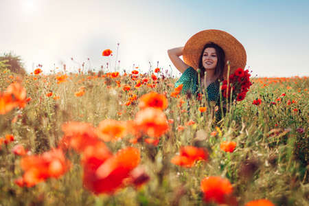 Young woman picking poppies flowers walking in summer field enjoying landscape. Stylish happy girl wearing straw hat