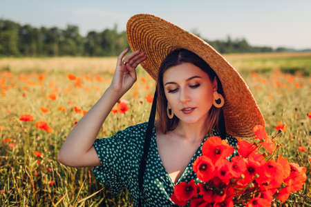 Portrait of young woman holding bouquet of poppies flowers walking in summer field. Stylish girl wearing straw hat Archivio Fotografico - 152824671