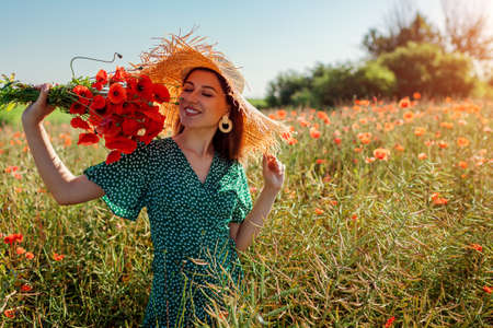 Young happy woman smelling bouquet of poppies flowers walking in summer field. Stylish girl wearing straw hat Archivio Fotografico