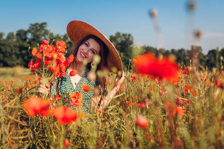 Young smiling woman picking bouquet of poppies flowers walking in summer field. Happy girl feeling free