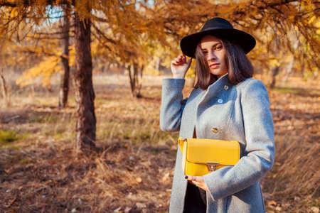 Autumn fashion. Young woman wearing stylish outfit and holding purse outdoors. Clothing and accessories