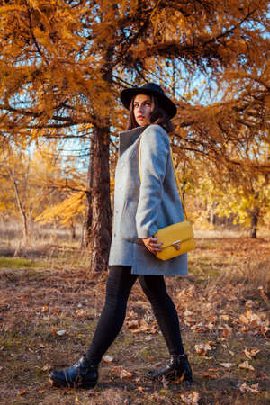 Autumn fashion. Young woman walking in park holding purse outdoors. Clothing and accessories
